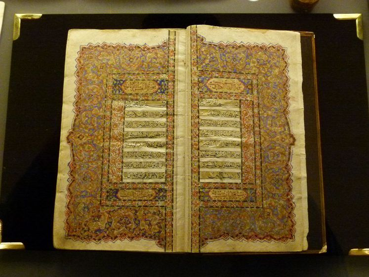 A Quran with geometric artwork in the margins of each page.