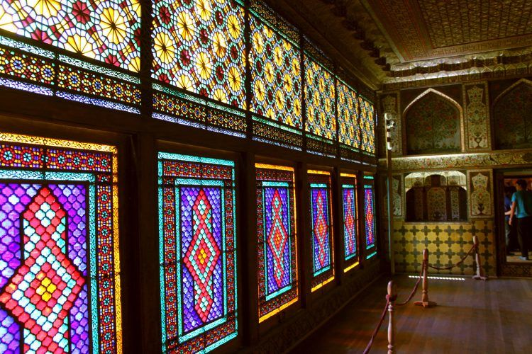 A small room with a floor-to-ceiling set of stained glass windows.