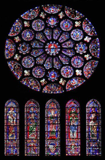 A circular stained glass window with five tall stained glass windows beneath it.