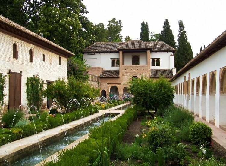 A long garden bisected by a long water feature, with buildings on all three sides.