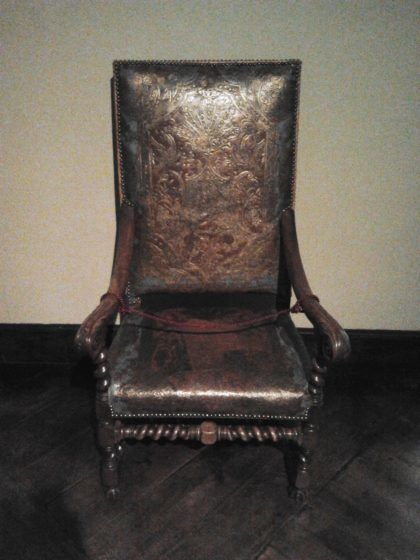 A chair with ornate leather covers.