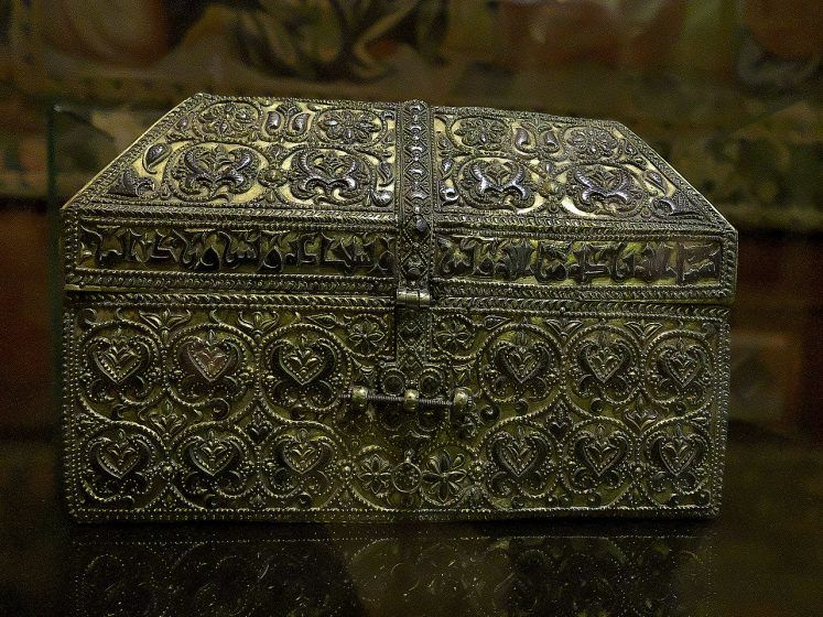 A silver and gold ornamental chest with Arabic inscriptions.