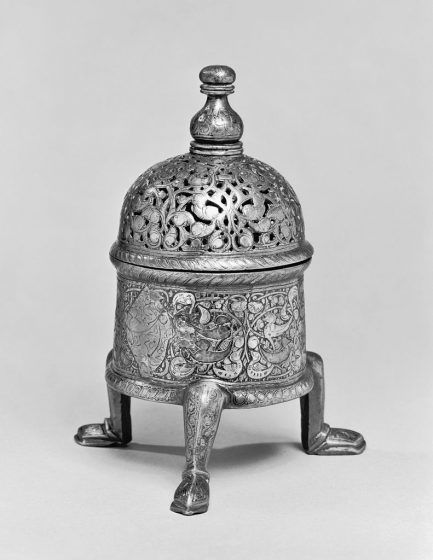 A silver round insence burner with three legs.