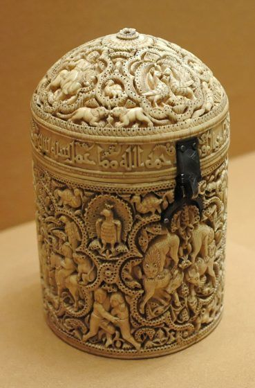 A cylindrical white ivory case with intricate drawings.