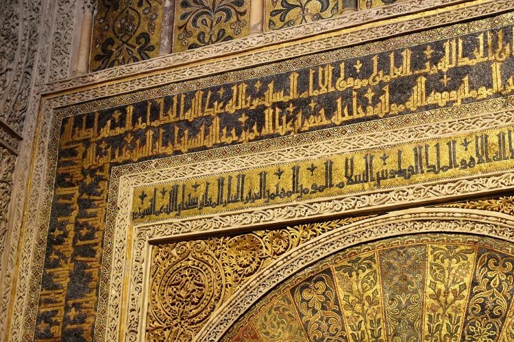 Ornate black and gold Arabic inscriptions on a corner of a wall.