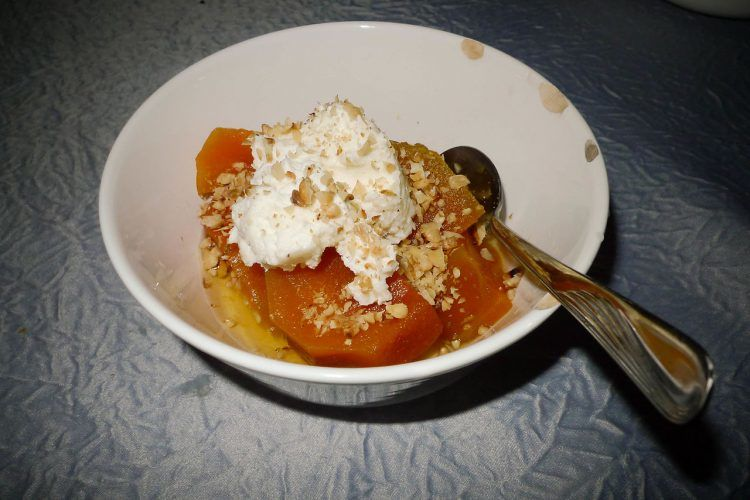 A pumpkin dessert in a bowl with kaymak and walnuts.