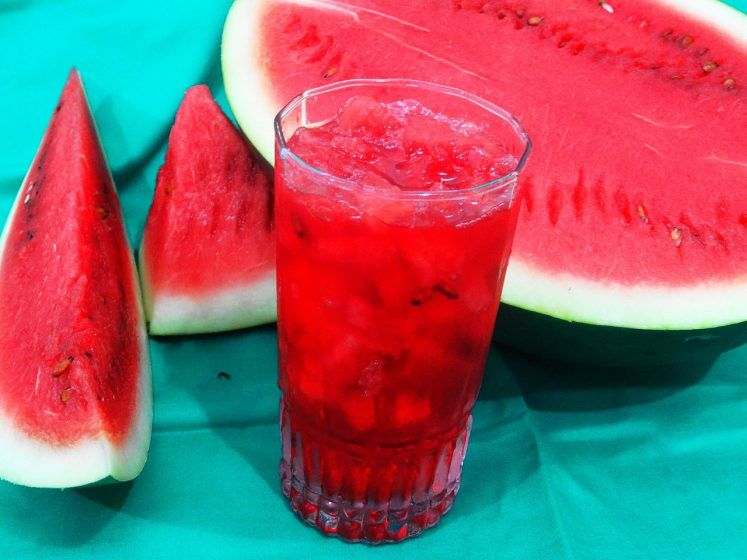 A glass of sharbat with watermelon in the background.