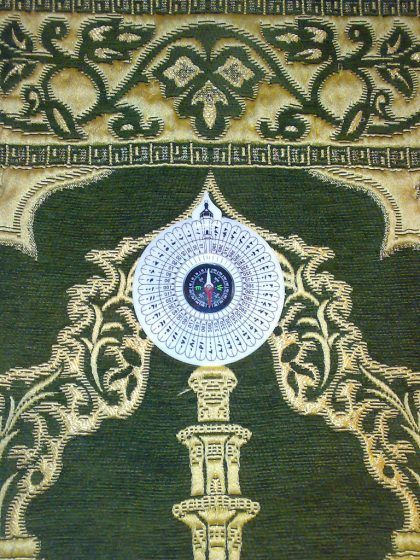 A white compass on a green and gold prayer rug.
