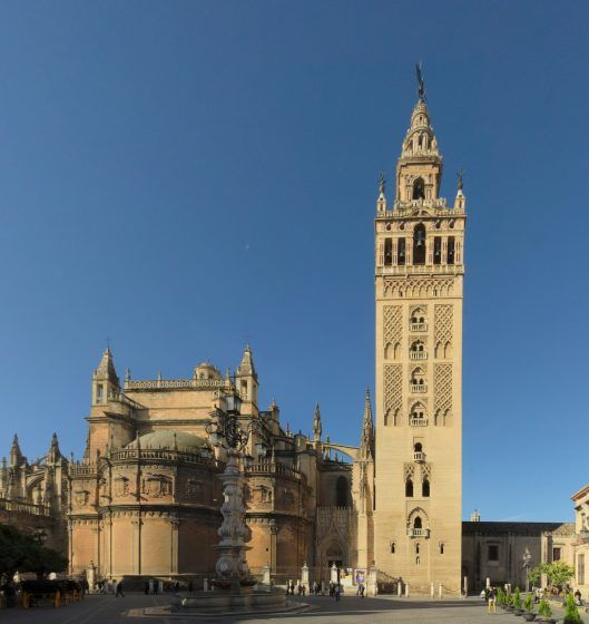 A large beige tower, the Giralda, next to a smaller building.