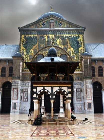A picture of the entrance to the Great Umayyad Mosque of Damascus showing a painting of greenery and buildings.