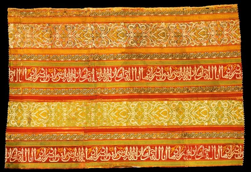 A bright yellow and orange silk textile with Arabic lettering.